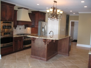 Custom Home Kitchen, Wall-Mounted Double Stack Ovens, Custom Range Hood, Center Island, Brass / Crystal Chandelier, Stainless Steel Appliances - Madison Custom Homes Inc., Indianapolis, Indiana