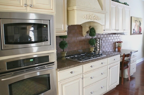 Custom Home Kitchen, Wall-mounted Double Stack Ovens, Granite Counters, Faux-Brick Backsplash, Custom Range Hood; - Madison Custom Homes Inc., Indianapolis, Indiana