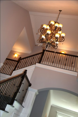 Luxury Home Foyer: Design Detail Close-up, Carpeted Hardwood Staircase, Wrought Iron and Oak Banisters, Crown Molding Accent; Luxury Homes Built to Your Specifications; Indianapolis, Indiana - Madison Custom Homes Inc.