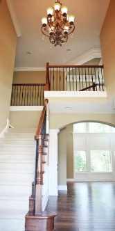 Carpeted Hardwood Staircase, Oak / Wrought Iron Banisters, Crown Molding Accents
