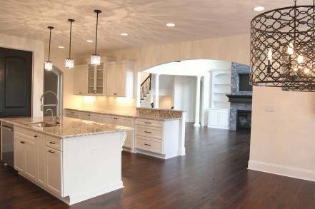 Kitchen with Island; Archway Leads into Great Room of Central Indiana Custom Home built by Madison Custom Homes Inc.